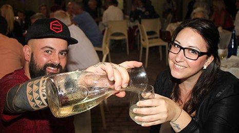 un ragazzo con un cappellino sta versando del vino sfuso in un bicchiere di una ragazza