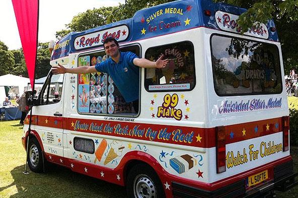 Happy employee standing in the ice cream van