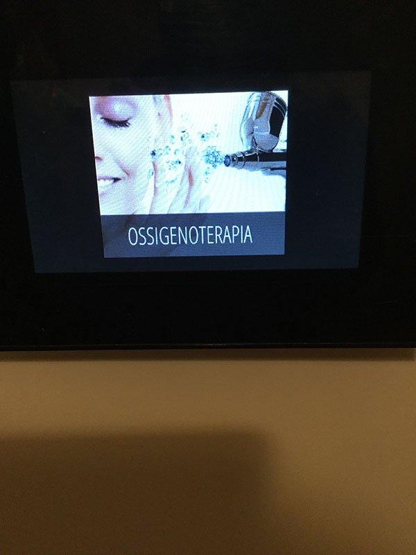 immagine di un volto di una donna con accanto un dispositivo che rilascia delle gocce d'acqua e sotto la scritta Ossigenoterapia