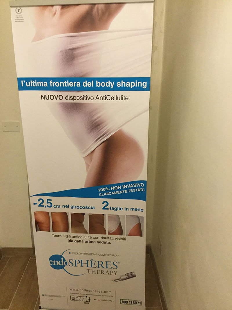 Un cartello pubblicitario con una donna e una scritta L'ultima frontiera del body shaping, nuovo dispositivo anti cellulite