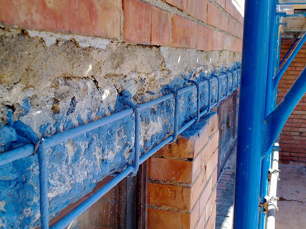 un muro di mattoni e una struttura di ferro verniciata di blu