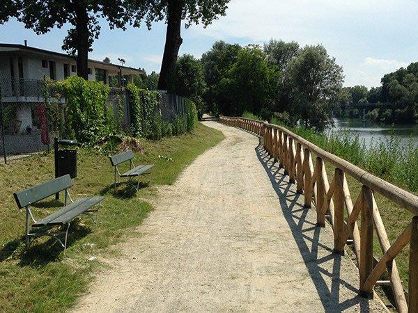 panchine e uno steccato in legno vicino a un laghetto