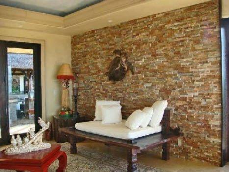 una struttura di legno con un piccolo materasso color panna e dei cuscini
