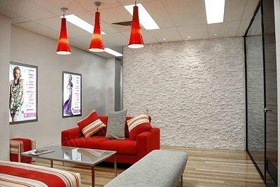 un salotto con un divano rosso, uno grigio e un tavolino di vetro