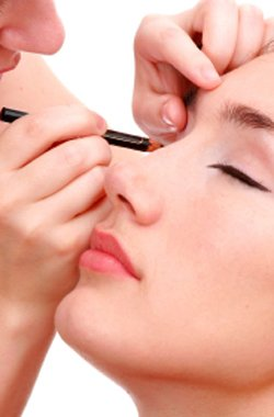 A woman applying eyeliner on another woman