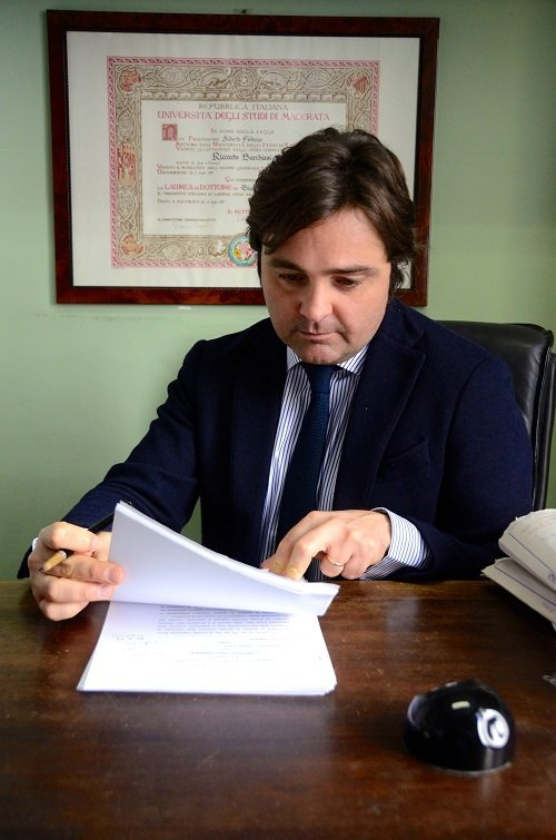 un signore alla scrivania che esamina un documento