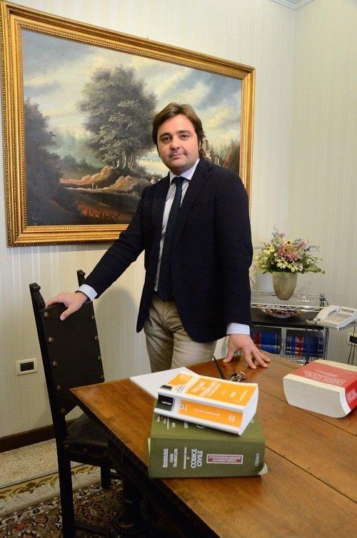 un signore in piedi vicino a una sedia e un tavolo