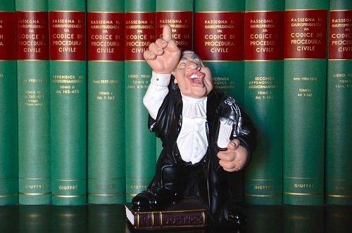 un pupazzetto di un giudice e dietro dei libri del Codice Civile