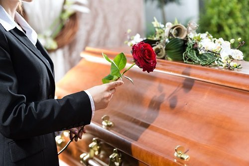 donna posa rosa su cassa funebre