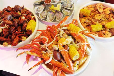 platter with crab legs, corn, and potatoes with onions