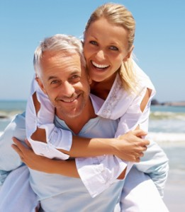 Smiling Woman Piggy Back Riding On a Smiling Mature Man
