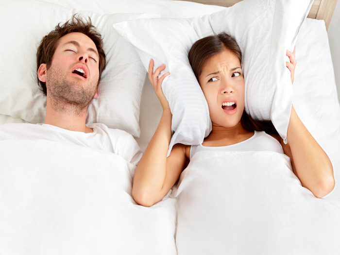 Upset Woman Covering Ears With Pillow and in Bed  With Snoring Man