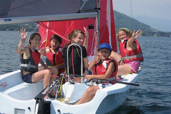 dei ragazzini su una barca vela con dei corsetti