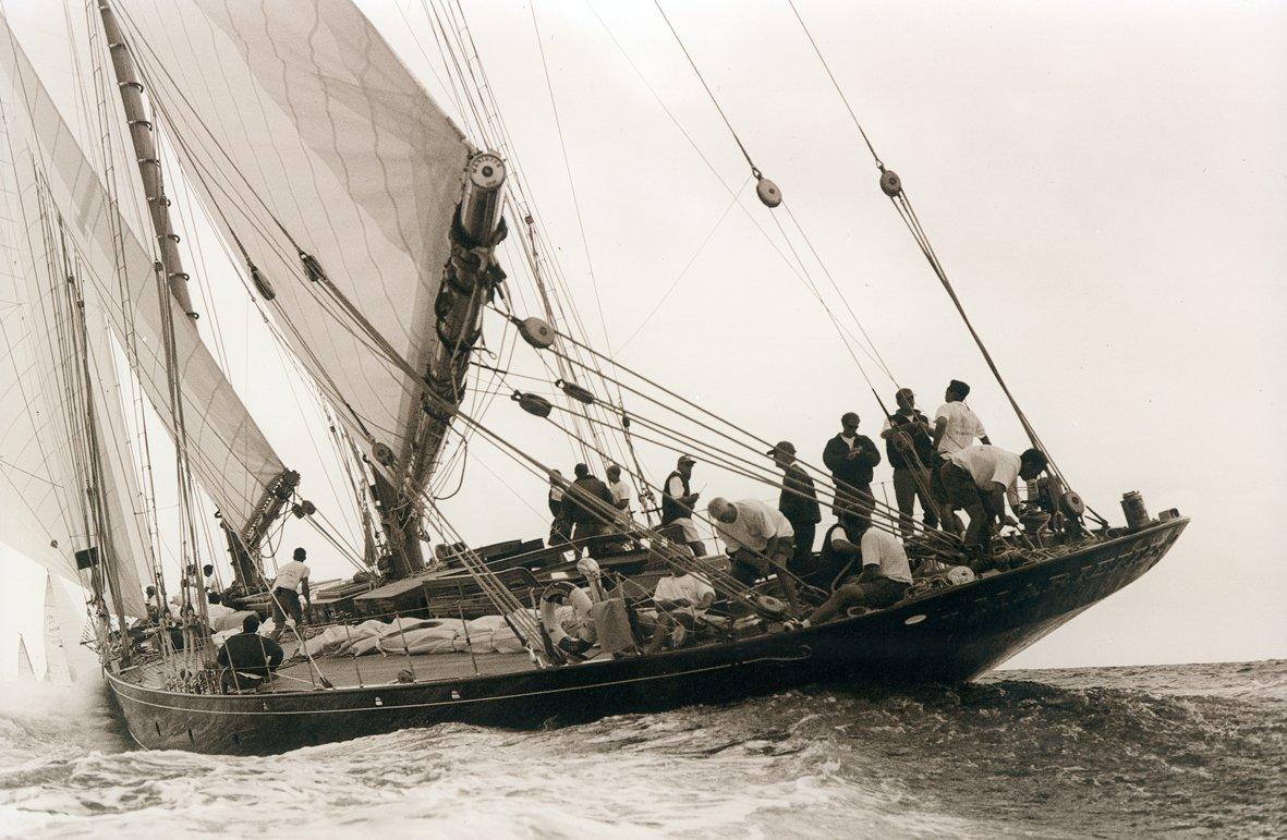 un'immagine in bianco e nero di alcune persone su una barca a vela in mare