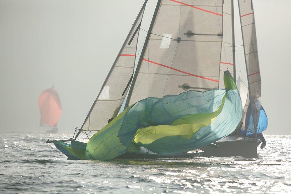 una barca a vela in mare con dei teloni verdi che svolazzano