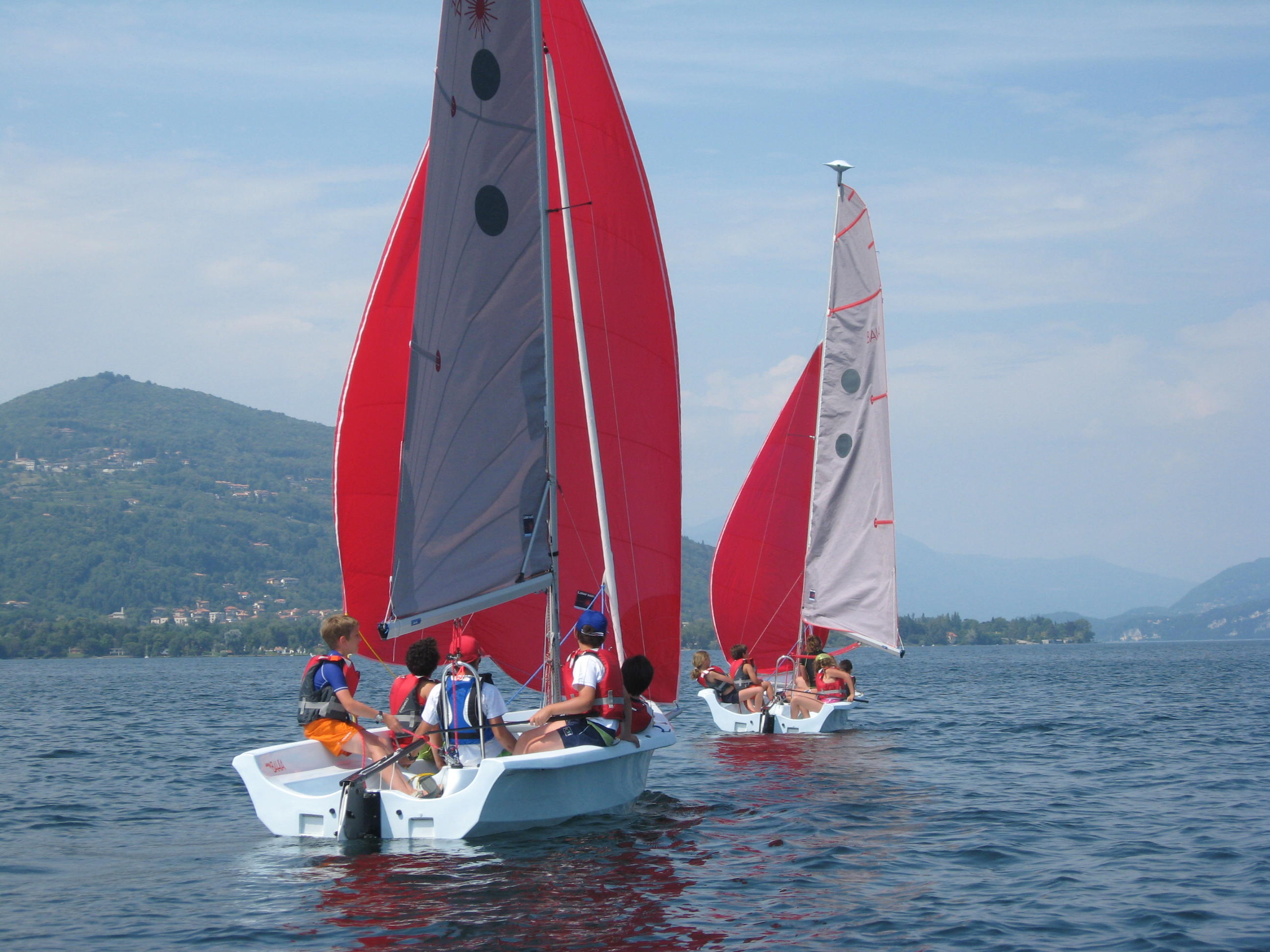 due barche a vela in acqua con su dei ragazzini e vista delle montagne