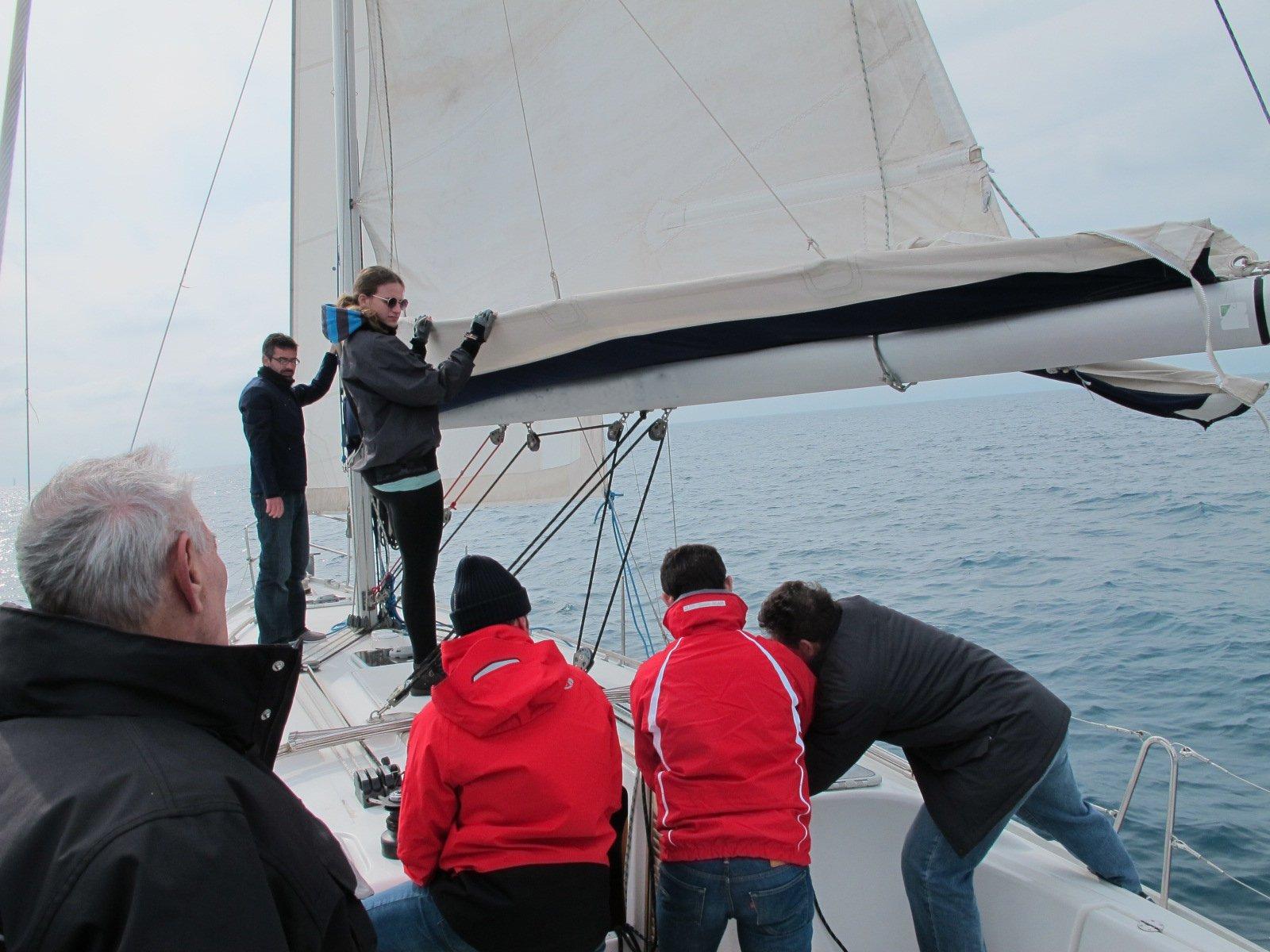 delle persone su una barca vela di cui uno appoggiato all'albero maestro