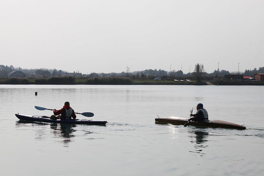 due persone con delle canoe in un laghetto