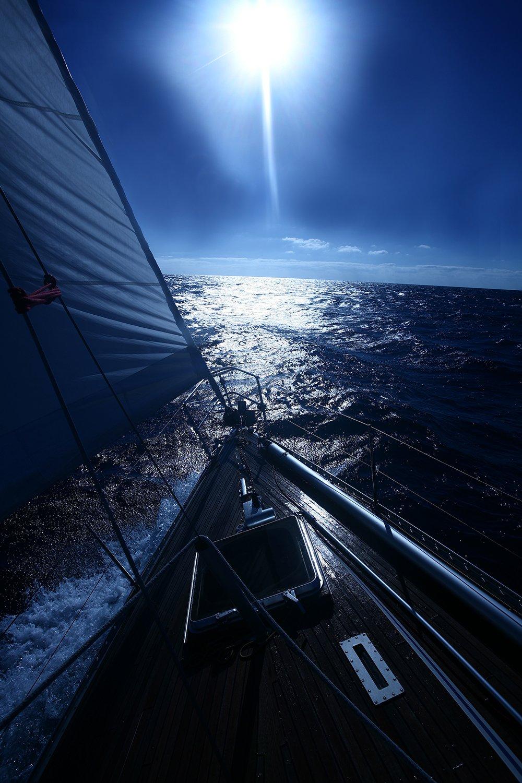 vista della prua di una barca in mare e in lontananza un faro acceso