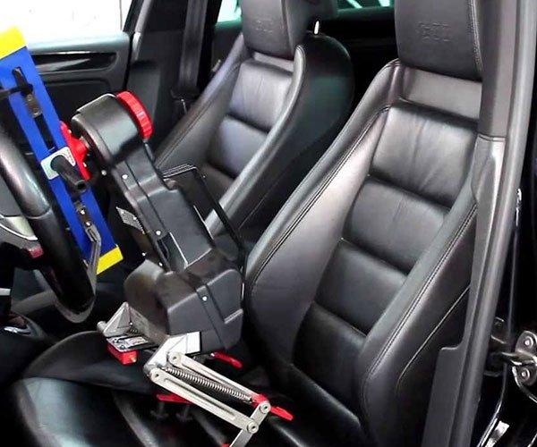 vista dei sedili in pelle all'interno di una macchina e un dispositivo attaccato al volante con dei morsetti
