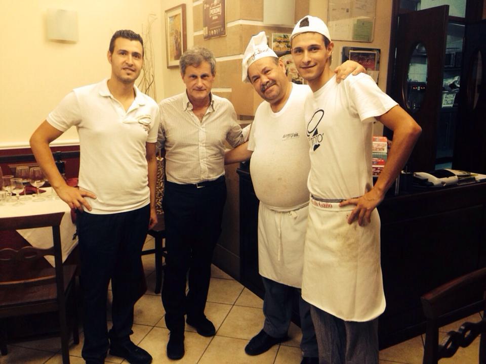 Quattro uomini abbracciati all'interno di un ristorante