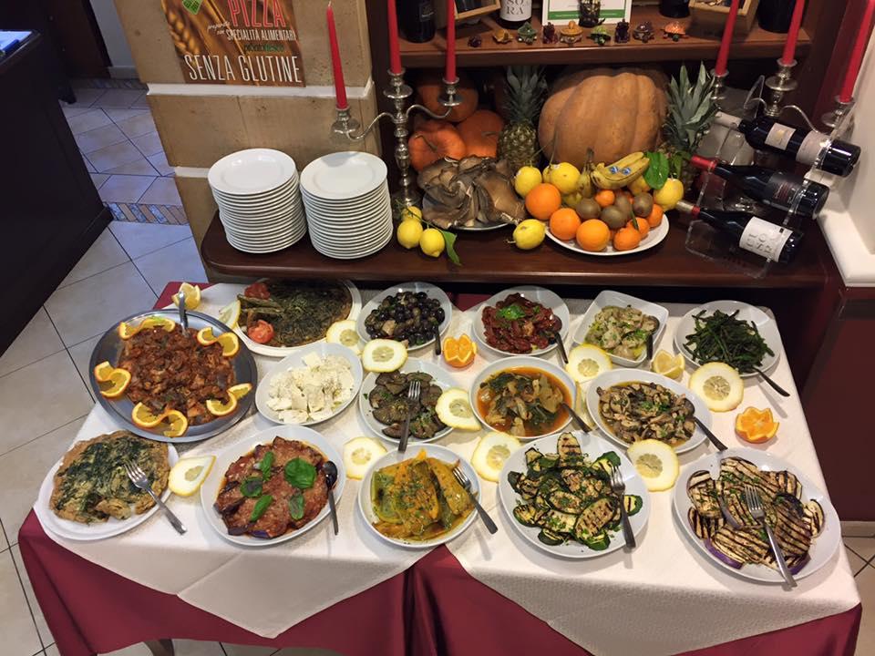 Un buffet con dei piatti pronti a base di verdura e una scritta sul muro Senza Glutine
