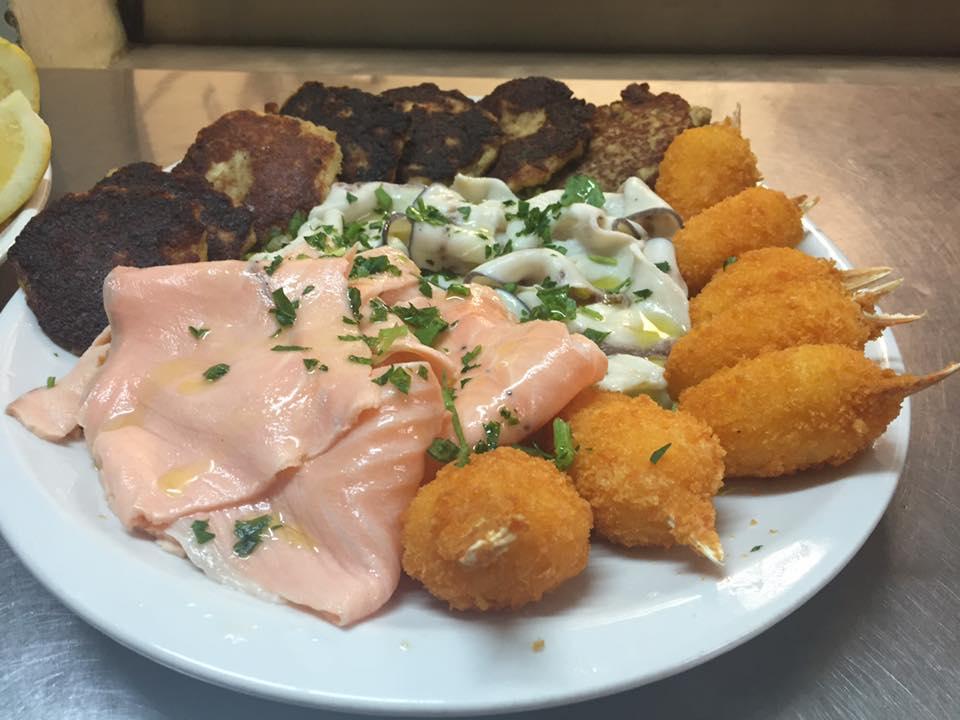 Un piatto con carpaccio di pesce, delle crocchette  e chele di granchio