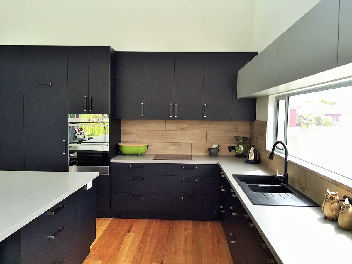 black kitchen with red flooring alternate view