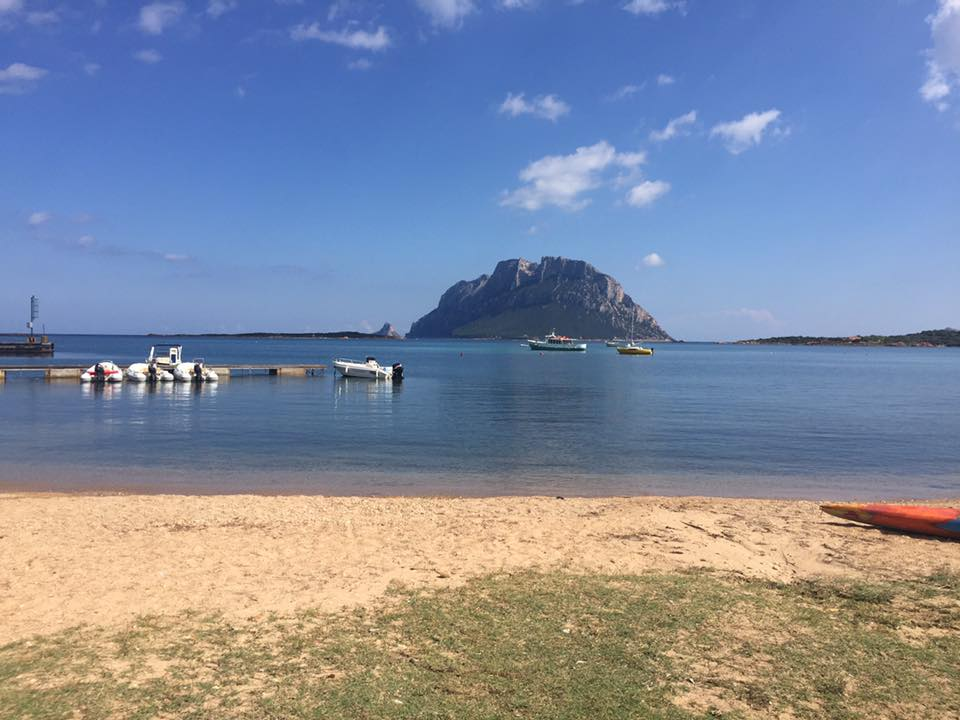 spiaggia con imbarcazioni sullo sfondo