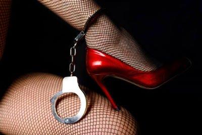 Calze nere a rete autoreggenti, scarpe rosse e manette nel caviglia