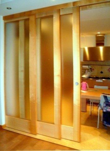 Porta interna scorrevole in tre parti realizzata in massello e vetro