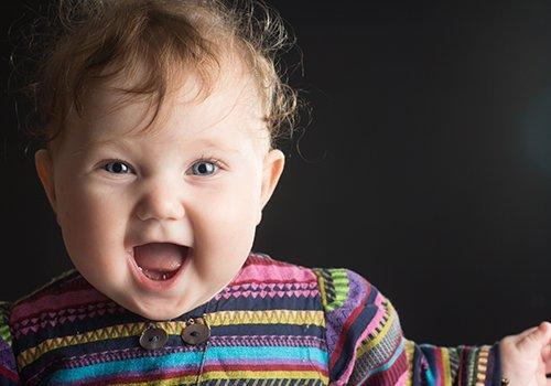 Neonata sorridente con vestitino colorato