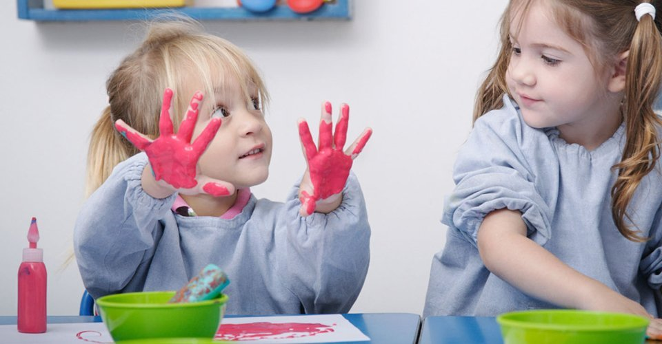 A little girl showing her pink-painted hands to another little girl