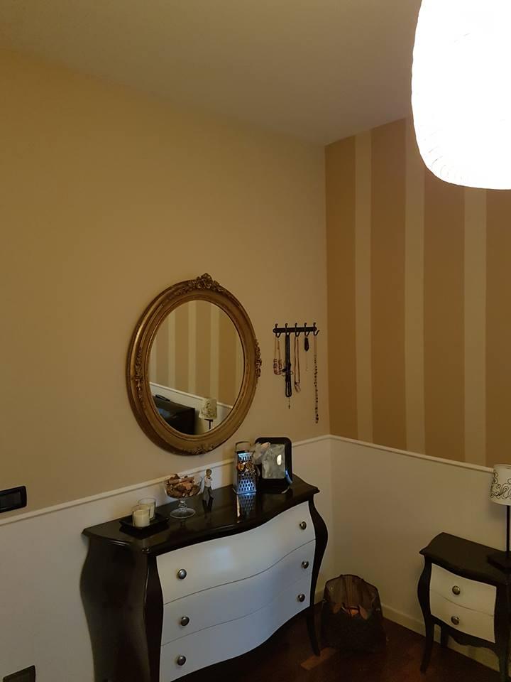 una stanza con un como', uno specchio dorato e muri a sfumature gialle