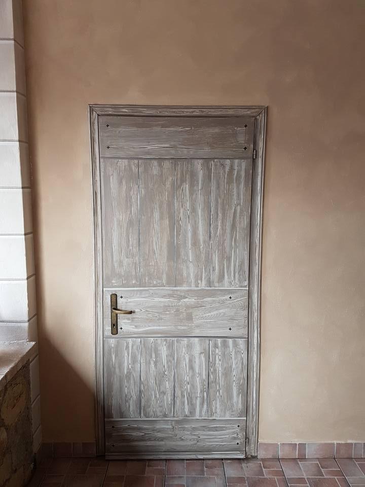 una porta in legno con sfumature grigie