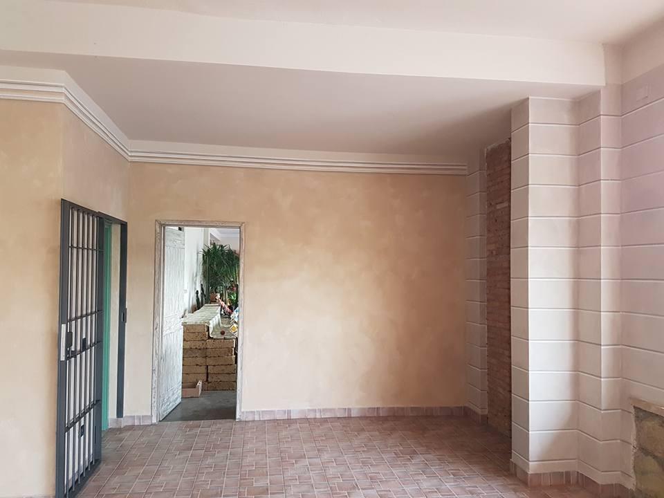 una stanza con muri dipinti color sabbia e vista di una porta aperta