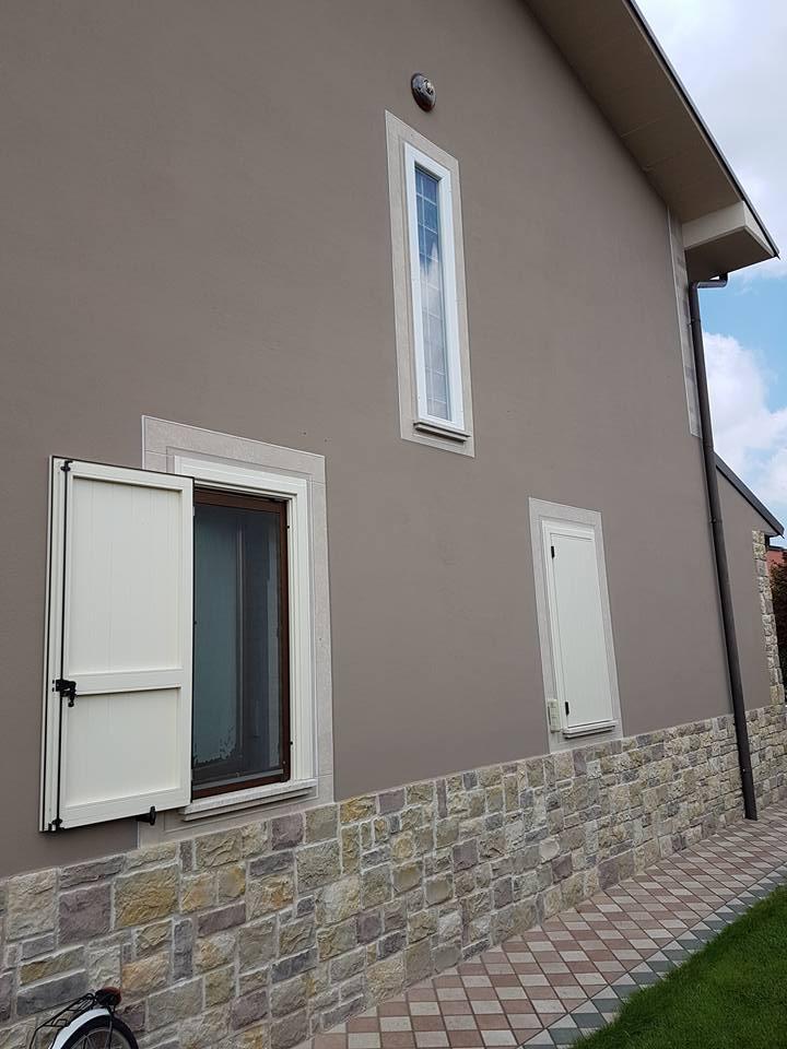 una facciata grigia di una casa con vista delle finestre con delle persiane bianche