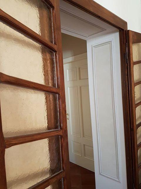 una porta in vetro con finiture in legno aperta uno stipite