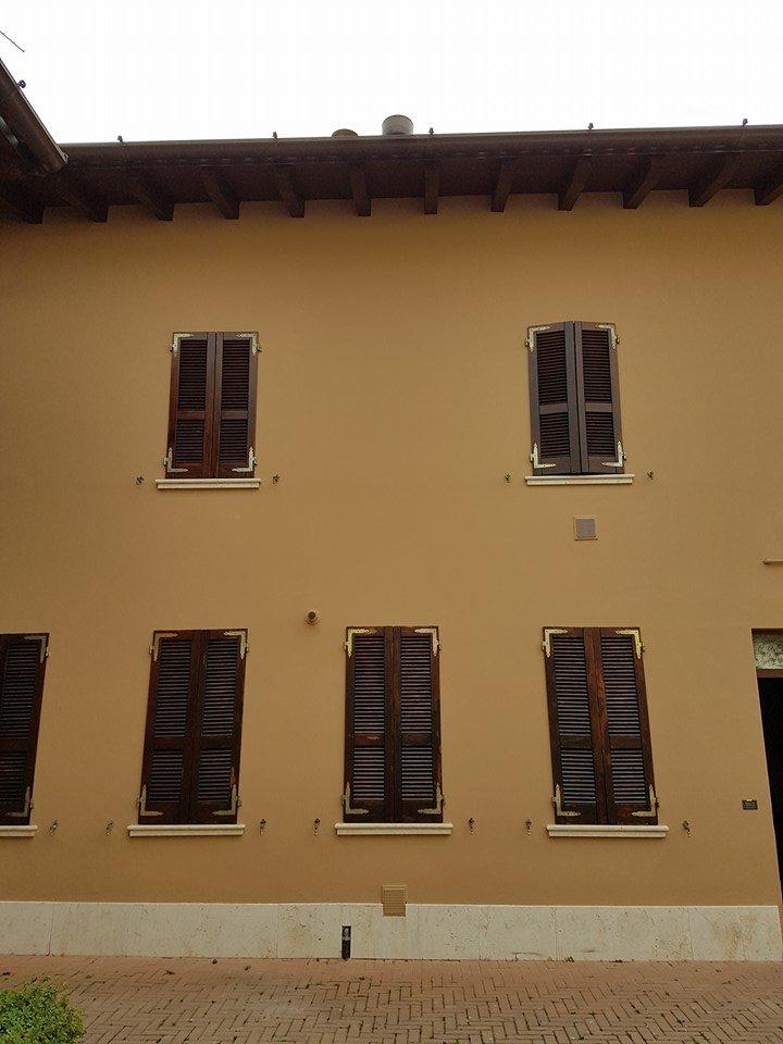 una casa gialla con vista delle finestre con delle persiane marroni