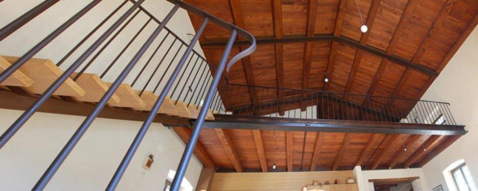 Scala interna di ferro e legno che si eleva maestosa e la cui semplicità riempie lo spazio