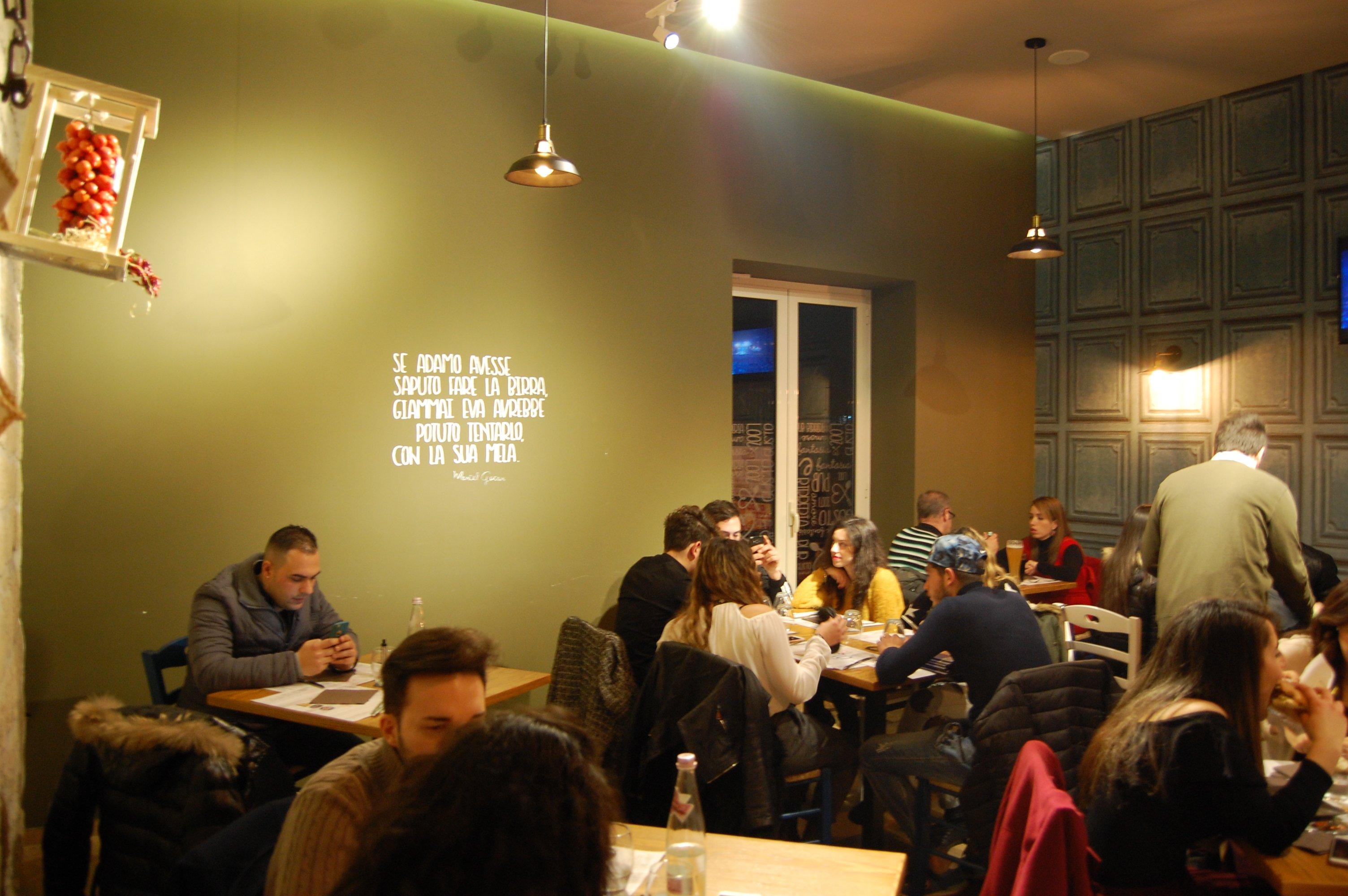 sala con i tavoli con muri verdi, condizionatore e finestre che permettono di vedere all'esterno