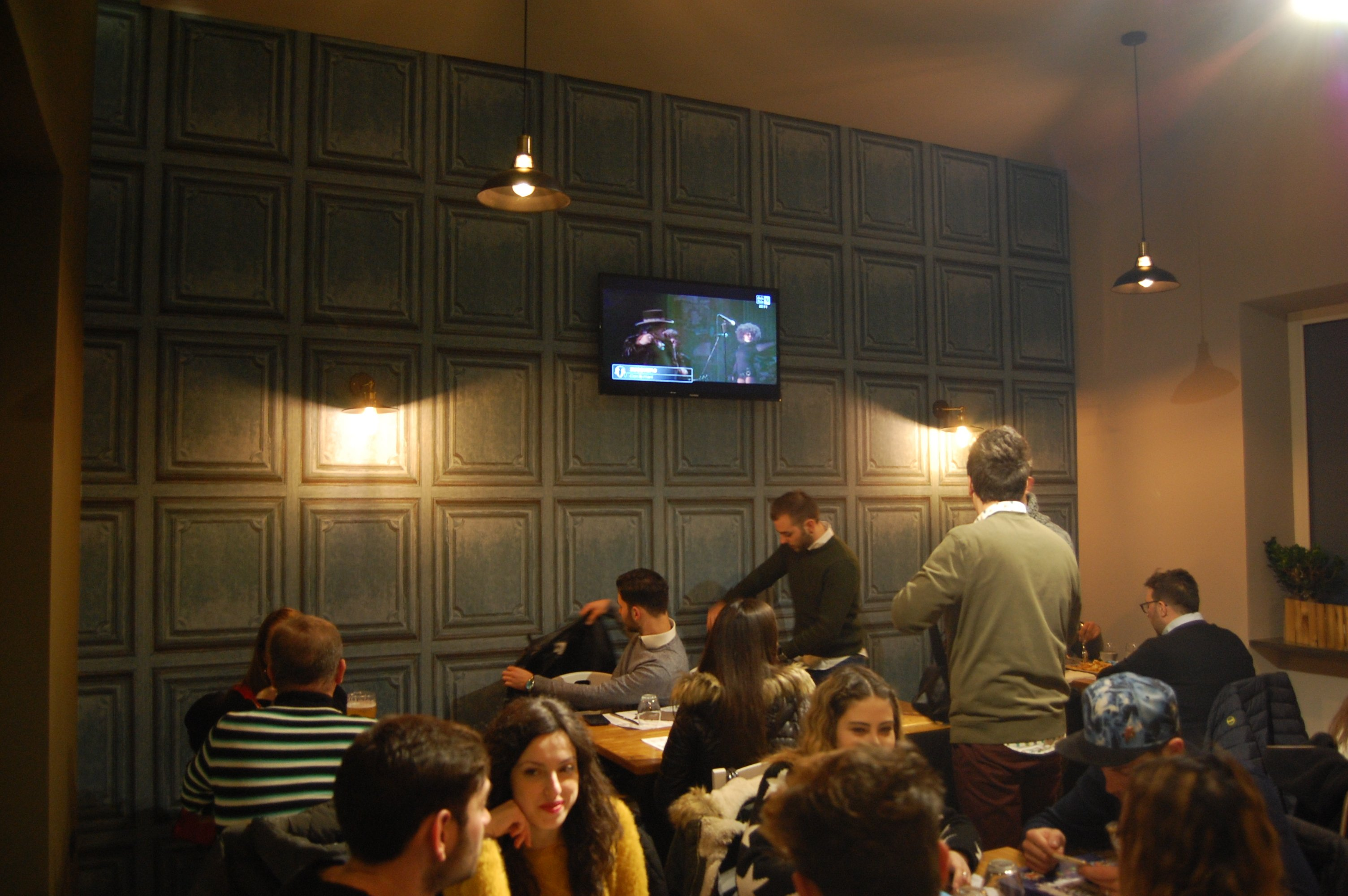 vista della sala con i tavoli con lampade a sospensione e la televisione