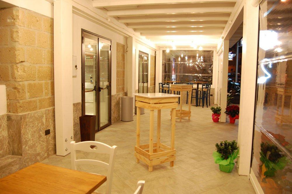 prima della porta di entrata tavolini alti in legno vasi di fiori e altri tavoli