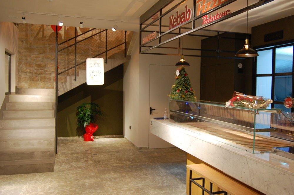 vista ravvicinata della pianta sotto il sottoscala e un cartello appeso allo scorrimano delle scale con scritto GUSTO TABLES ROOM