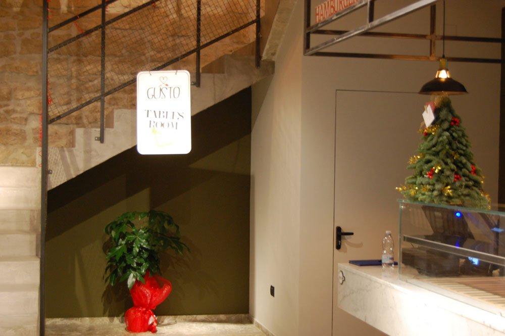 il bancone con le vetrine, un sottoscala con una pianta e delle scale che portano al piano superiore