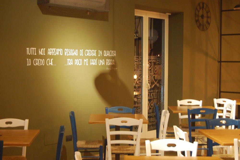 muro di color verde e frase dipinta TUTTI NOI ABBIAMO BISOGNO DI CREDERE IN QUALCOSA..IO CREDO CHE.. TRA POCO MI FARO' UNA BIRRA