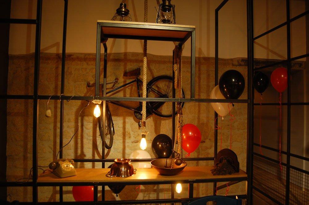 bicicletta appesa al muro, corde pendenti, lampadine e un tavolo con delle lanterne sospeso in aria