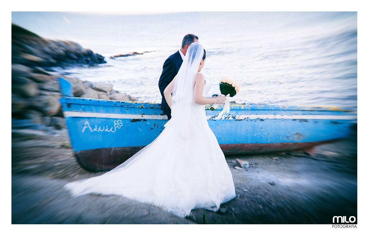 foto di uno sposo e una sposa su una riva con una barca accanto