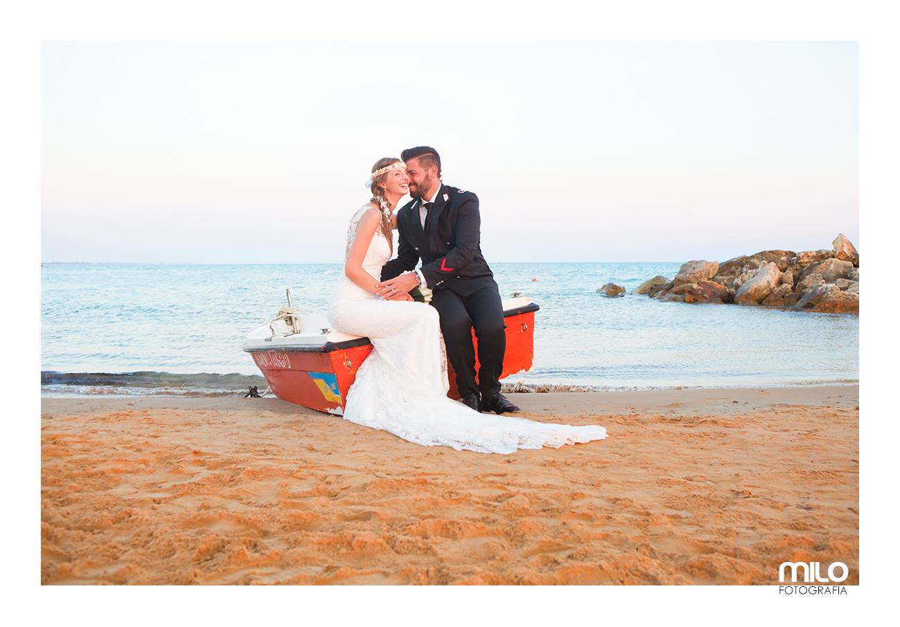uno sposo e una sposa seduti su una barca sulla riva del mare