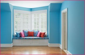 Blue decorated room with coloured cushions.